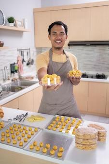 Man met zijn kookkunsten die naar de camera lacht en thuis nastar-cake maakt voor eid mubarak