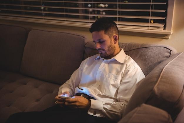 Man met zijn mobiele telefoon in de woonkamer