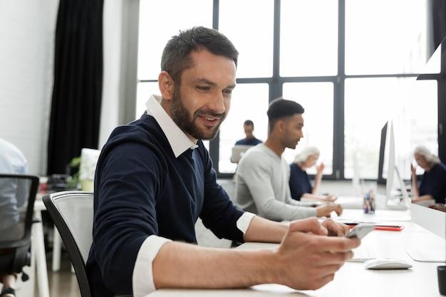 Man met zijn mobiele telefoon zittend aan zijn bureau