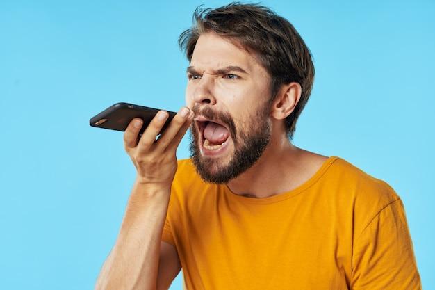 Man met zijn mond wijd open houdt een mobiele telefoon in zijn hand
