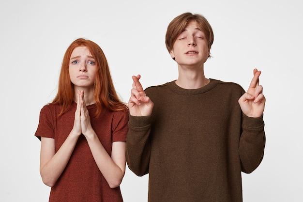 Man met zijn ogen dicht, vingers gekruist, doet een wens, hoopt op gelukkige omstandigheden.