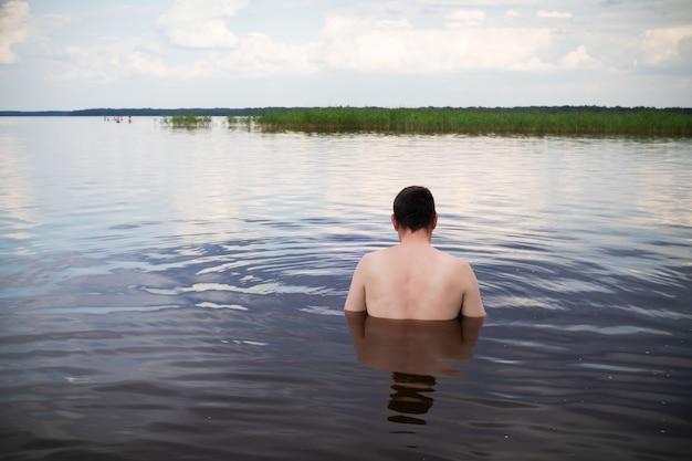 Man met zijn rug in het meer, de rivier of de zee bij bewolkt weer.