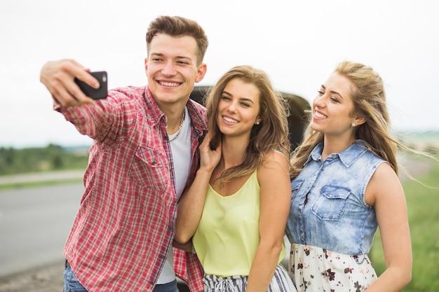 Man met zijn twee vrouwelijke vrienden nemen zelfportret op mobiele telefoon