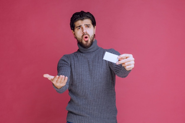 Man met zijn visitekaartje en kijkt verbaasd.