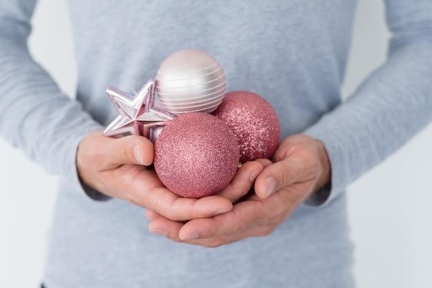 Man met zilver en rose goud glitter kerstballen in handen.