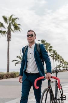 Man met zonnebril die zijn fiets buiten houdt