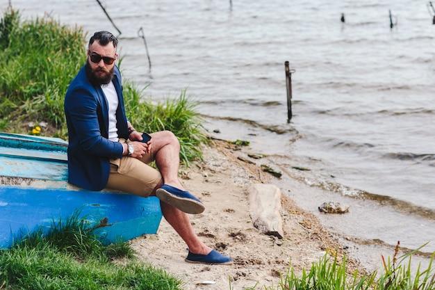 Man met zonnebril, zittend op een houten boot