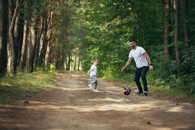 Man met zoontje die samen voetbal speelt en een bal graaft in het bos, samen tijd doorbrengen met een leuk weekend