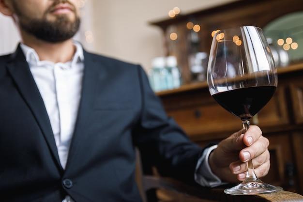 Man met zwart pak met een glas rode wijn