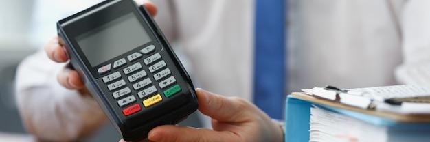 Man met zwarte geldautomaat in zijn handen in kantoorclose-up