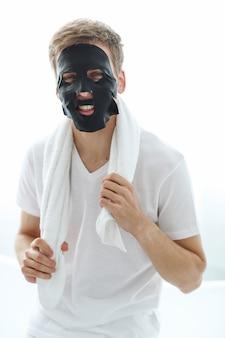 Man met zwarte gezichtsmasker, huid zuiverende houtskool. schoonheid concept