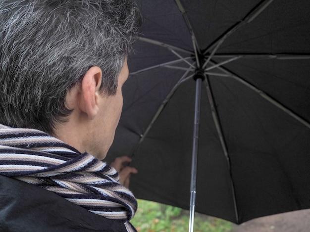 Man met zwarte paraplu in het park.