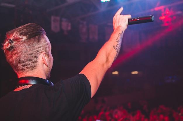 Man met zwarte t-shirt met microfoon op het podium omringd met mensen kijken