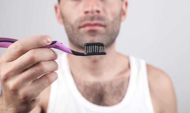 Man met zwarte tandpasta en tandenborstel