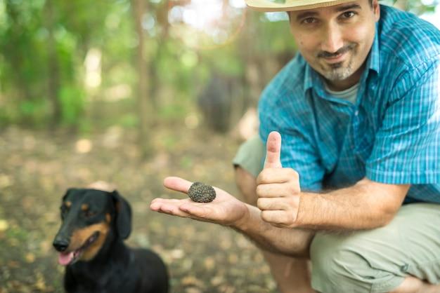 Man met zwarte truffel met duim omhoog in de natuur.