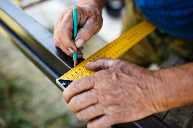 Man meten van metalen staaf in werkplaats.