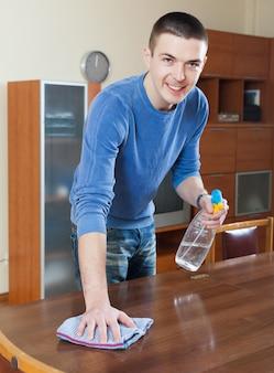 Man meubels schoonmaken met cleanser en vod in de woonkamer