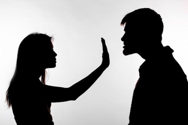 Man misbruikt vrouw, silhouet op een witte achtergrond.