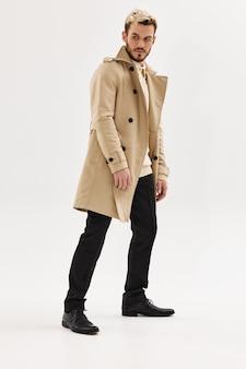 Man modieus kapsel beige jas zijdelingse blik geïsoleerde achtergrond