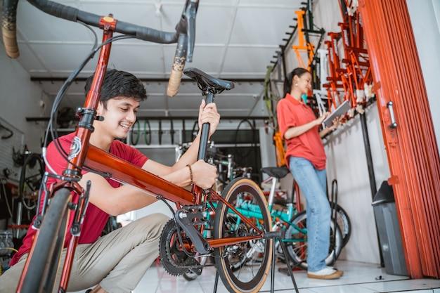 Man monteert fietszadelpen met vrouw op de achtergrond