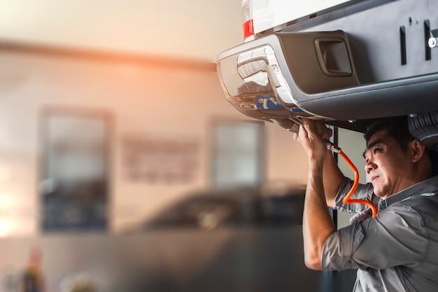 Man monteur inspectie service onderhoud auto schorsing verandering wielen. opmerking of schrijven voor controle en hand wijzend. motor controleren in garage showroom dealer