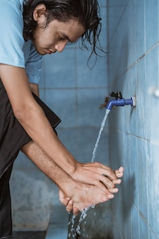 Man moslim verricht wassing (wudhu) voet wassen voor het gebed