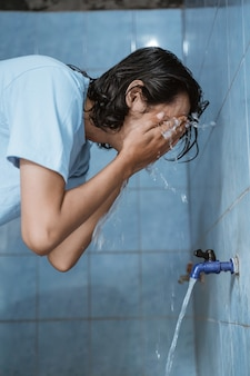 Man moslim voert de wassing (wudhu) uit en wast het gezicht voor het gebed
