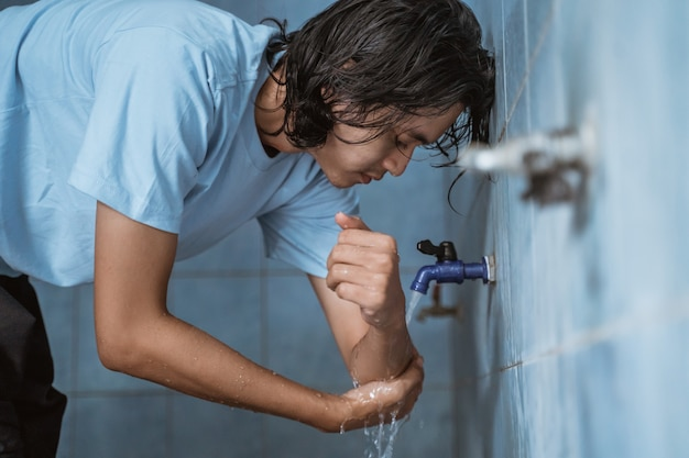 Man moslim voert wassing (wudhu) uit en wast de hand voor het gebed