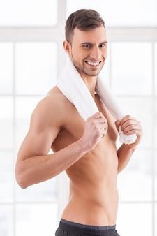 Man na training. knappe jonge gespierde man met handdoek op schouders camera kijken en glimlachen