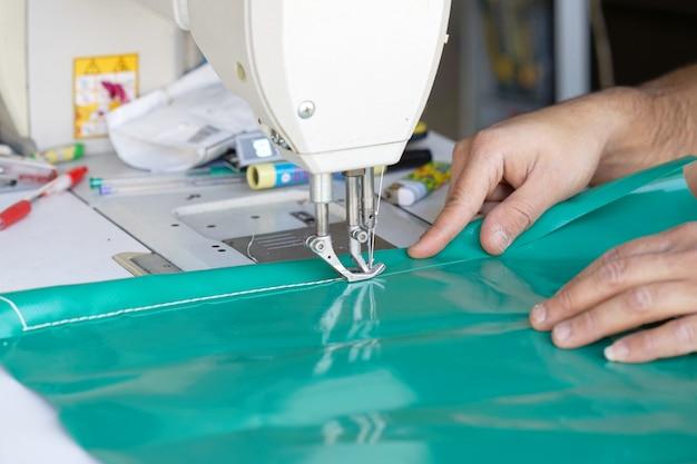 Man naaister. mannen handen achter het naaien van leer.
