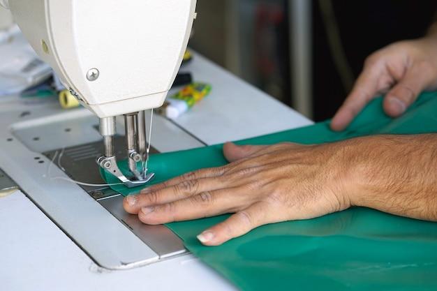 Man naaister. mannenhanden achter het naaien van leer.