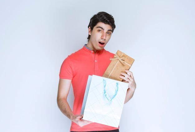 Man neemt een kartonnen geschenkdoos uit een boodschappentas met een verrassing in zijn gezicht.