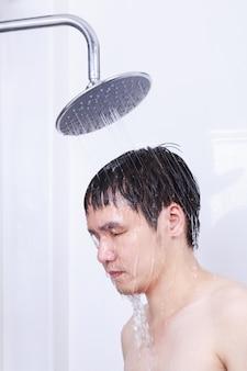 Man neemt een regendouche in de badkamer
