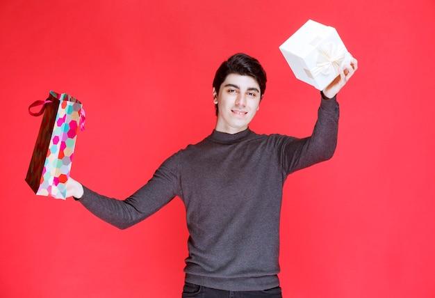 Man neemt een witte geschenkdoos uit een kleurrijke boodschappentas