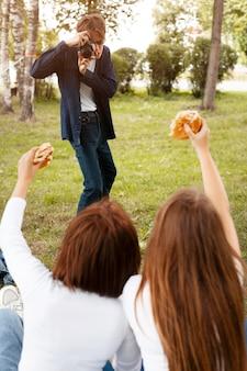 Man neemt foto van zijn vrienden terwijl ze hamburgers vasthouden