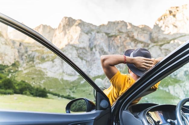 Man neergelegd op de motorkap terwijl u geniet van het uitzicht op de natuur.