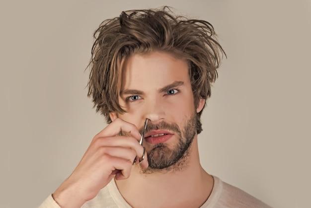 Man neushaar trimmen met een schaar en een pincet