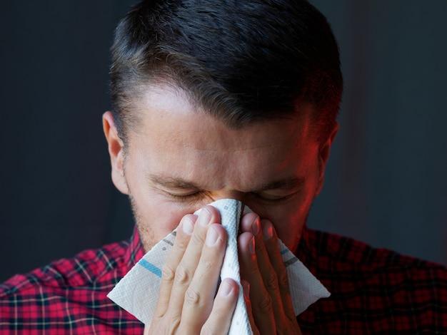 Man niezen gebruiken een servet. voorzorgs- en preventiemethoden om de verspreiding van het pandemische virus te voorkomen.