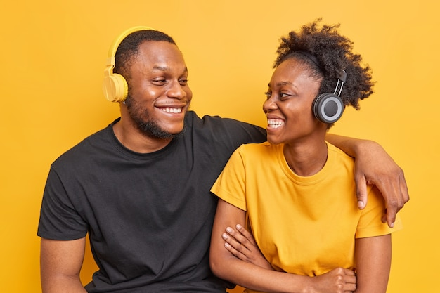 Man omarmen en kijken met een brede glimlach naar elkaar luister muziek via koptelefoon gekleed in casual t-shirts geïsoleerd op levendig geel
