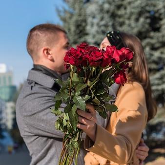 Man omhelst en vrouw met bloemen omhelzen