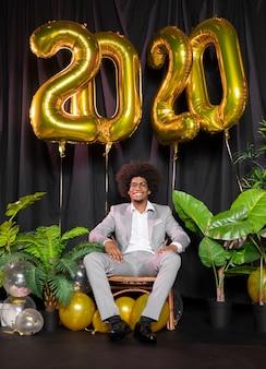 Man omringd door gelukkig nieuwjaar 2020-ballonnen