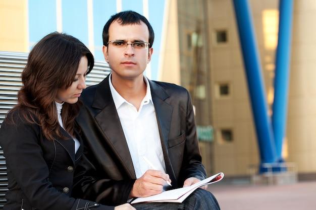 Man ondertekent documenten in de handen van een vrouw die op straat zit voor een kantoorgebouw