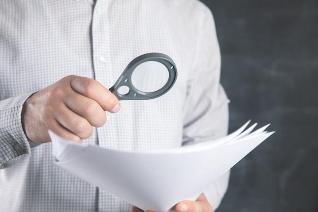 Man onderzoekt documenten met een vergrootglas.
