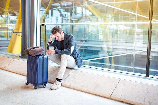 Man ongelukkig en gefrustreerd op de luchthaven zijn vlucht is geannuleerd