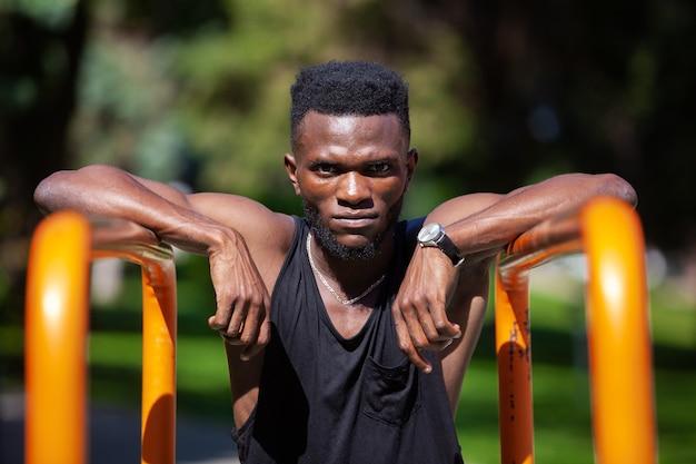 Man ontspannen in de buurt van sportartikelen na een training buiten in een park