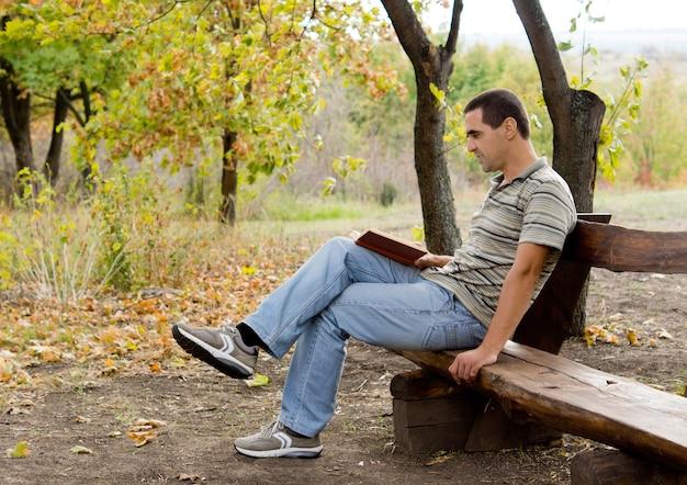 Man ontspannen met een boek zittend op een rustieke houten bank met een bosrijke achtergrond terwijl hij ontspant en geniet van zijn vakantie