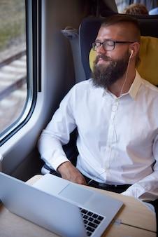 Man ontspannen met koptelefoon in de trein