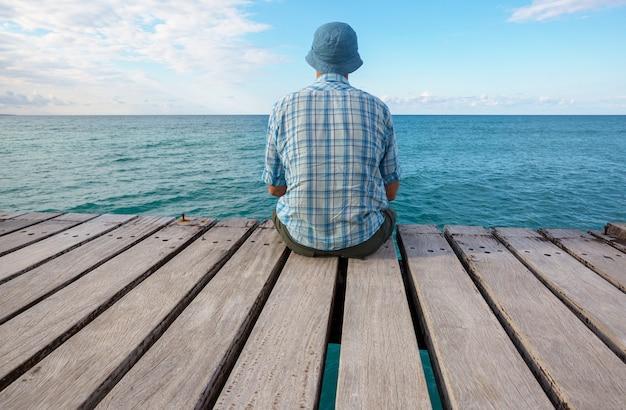 Man ontspannen op zee pier
