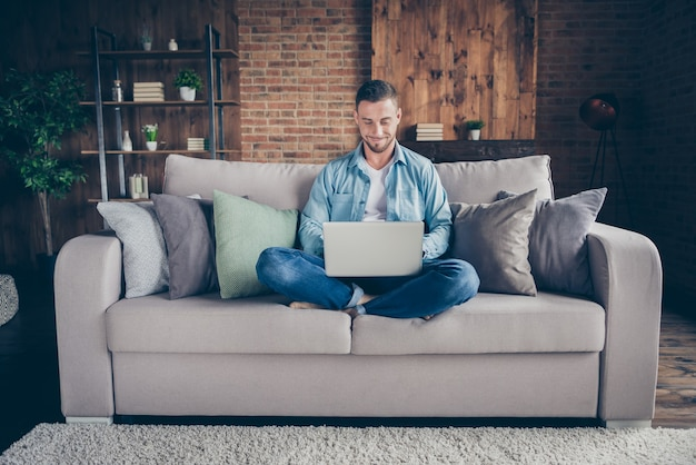 Man ontspannen zitten comfortabele bank benen gekruist browsen notebook
