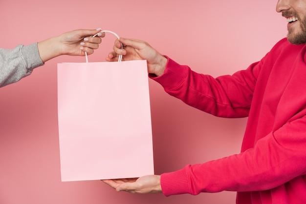 Man ontvangt een papieren, roze tas.